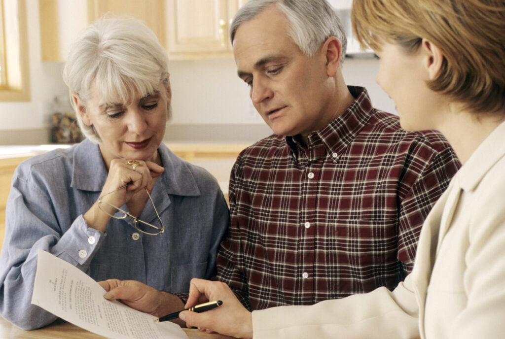 Mature couple talking to funeral planner at home about prepaid funerals